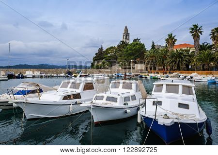 Boats in the harbor of Lopud Island with the Franciscan monastery on the background, Croatia