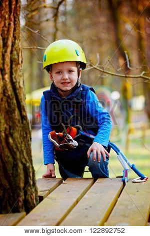 Portrait of happy little boy having fun in adventure park smiling to camera wearing helmet and safety equipment