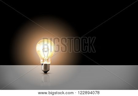 One incandescent light bulb on white table with black background. Front view. Horizontal composition