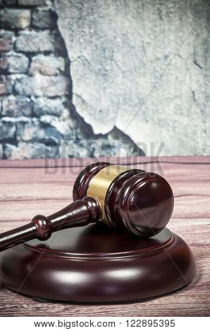 Wooden gavel on a vintage wall background
