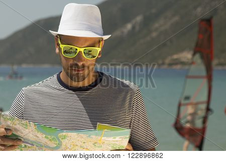 Guy trying to find the right direction by using his map. Windsurfer in the background.