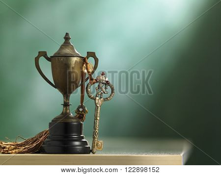 key with tassel and trophy in front of the blackboard
