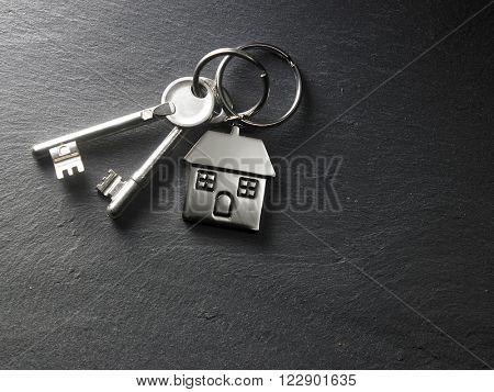 house shaped key chain on the black slate