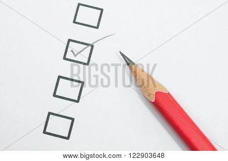 checklist box and red pencil on white paper.