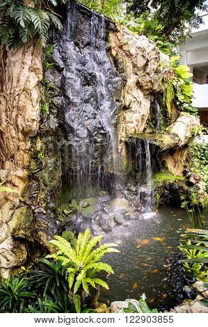 Small waterfall and pond with a koi carps fish in  Pattaya, Thailand.
