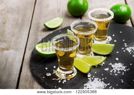 Still life, food and drink, holidays concept. Gold mexican tequila shot with lime and salt on a grunge wooden table. Selective focus