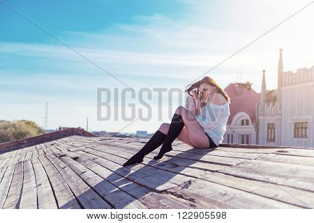 Pretty young sexy woman sitting on the wooden roof against the sky and sunlight