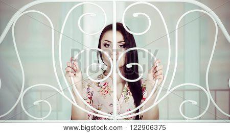 Beautiful sad woman with long hair behind bed bars