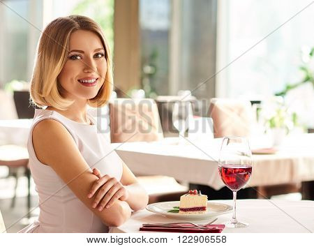 Enjoying the day. Stunning young woman is sitting at the restaurant and waiting for somebody.