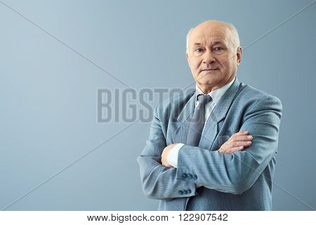 Serious and confident. Shot of thoughtful old man standing with his hands crossed and looking assertive.