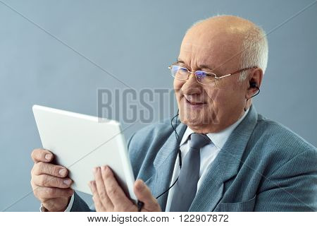 Internet technologies in business. Close up shot of old smart man with earphones holding tablet and looking interested.
