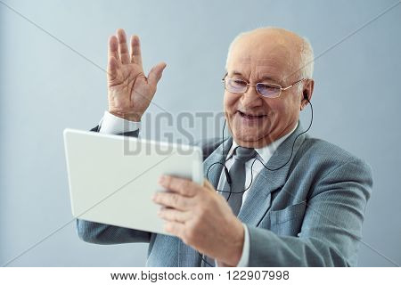 Business communications. Shot of nice old man looking friendly and making waving gesture while holding tablet.
