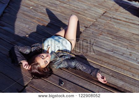 Pretty young brunette sexy woman lying on the wooden roof