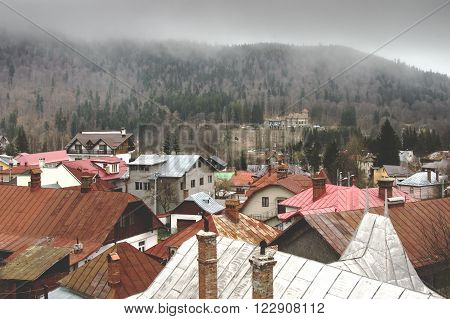 Busteni, ROMANIA - March 12 2016: Cantacuzino castle and rooftops in Busteni in a cloudy day.