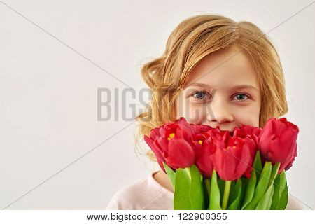 Fresh and cute. Portrait of  lovely blond girl holding  bouquet of tulips against white background.