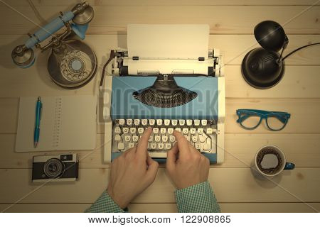 Journalist working on typewriter at his desk. No recognizable person. Top down view point. Along with typewriter there are eyeglasses, notebook, ball pen, cup of coffee, telephone, lamp and retro camera on the table