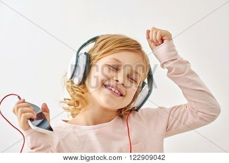 Dancing to sound. Little happy girl dancing around while listening to songs on her headphones in studio, isolated on white background
