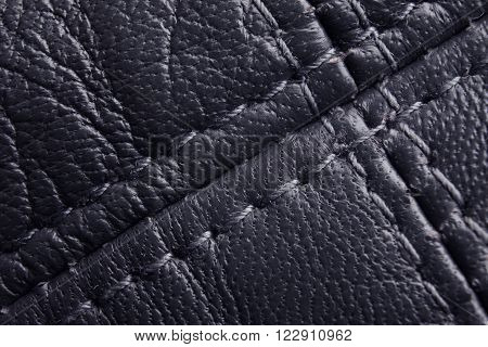 Navy leather macro background. Diagonal stitching detail