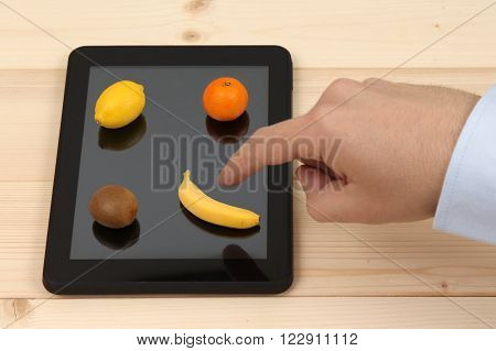 Male forefinger choosing the fruit on tablet device. Size of the fruits are decreased - digital tablet device icons concept.