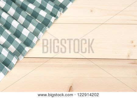 Wooden table with green picnic tablecloth and copyspace