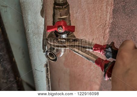 Plumber man replaces the tap in the bathroom. Fasten faucet using a wrench to rusty water pipe