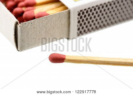 Matchbox, a small paperboard box enclosing a quantity of matches in the interior tray and having a coarse striking surface on the exterior. With a matchstick outside box isolated on white background.