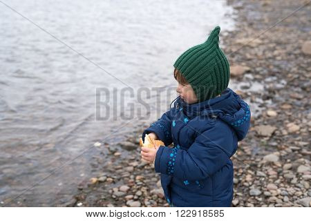 Little girl with a piece of bread on a river bank