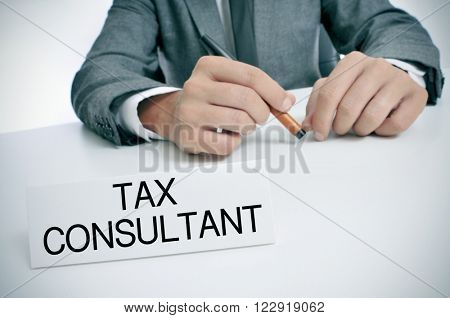 a man wearing a gray suit sitting at his office desk with a signboard in front of him with the text tax consultant written in it