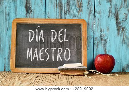 a chalkboard with the text dia del maestro, teachers day written in Spanish, a piece of chalk, an eraser and a red apple on a rustic wooden table, with a retro effect