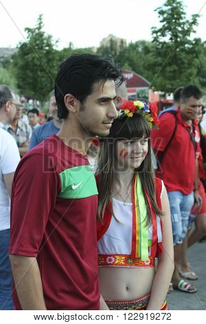 DONETSK UKRAINE - JUNE 27 2012: Unidentified Portugal soccer fan with Ukrainian girl before UEFA EURO 2012 match in Donetsk near Donbass Arena