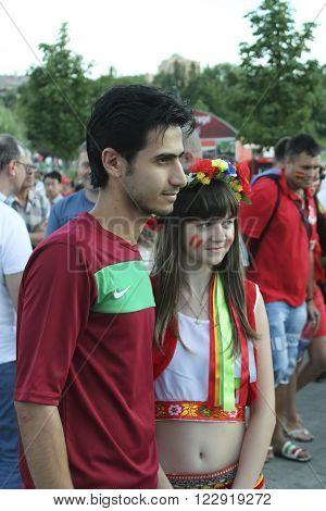DONETSK UKRAINE - JUNE 27 2012: Unidentified Portugal soccer fan with Ukrainian girl before UEFA EURO 2012 match in Donetsk near Donbass Arena