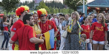 DONETSK UKRAINE - JUNE 23 2012: Unidentified Spanish soccer fans with Ukrainian girl before UEFA EURO 2012 match in Donetsk near Donbass Arena