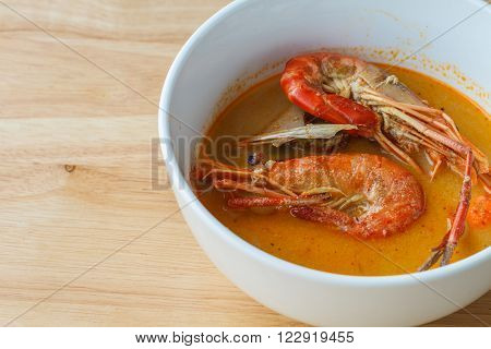 Thai spicy soup shrimp Bowl of spicy Thai Tom Yum Soup on wooden background