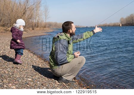 Man dropping a stone into the river. His daughter is stayibg nearby