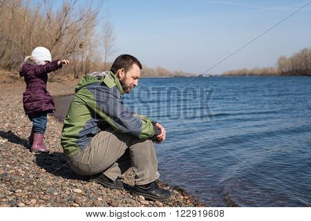 Girl dropping a stone into river. Her father is sitting nearby on a riverbank