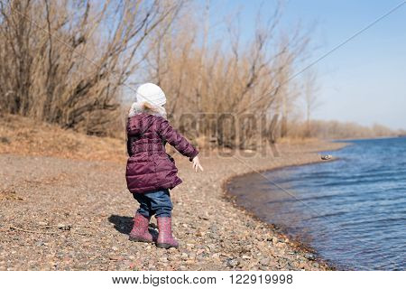 Little girl throwing stones into river in spring