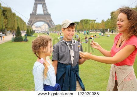 Mother, son and daughter with lollipops near in Paris