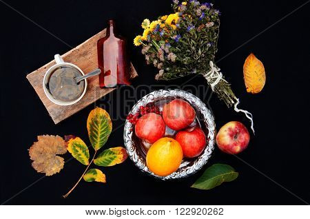 ripe apples in a beautiful plate black backgroundabove view a bouquet of wildflowers autumn leaf yellow-green thick brown bottle fruit red apples in a silver plate lemon yellow red viburnum