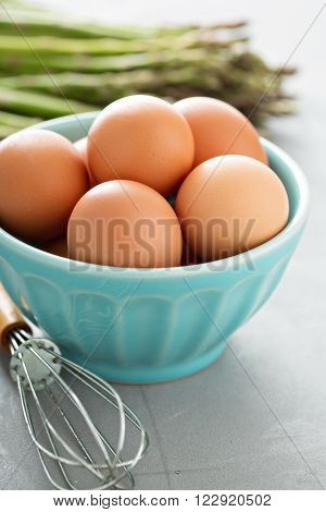 Fresh eggs in a bowl with a whisk and asparagus in background