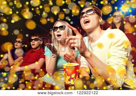 Young people sitting at the cinema, watching a film. Cinema photo series