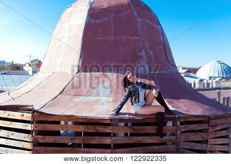 Pretty young sexy woman sitting on the rusty roof peak