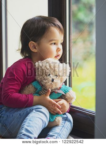 little girl looking at the window .