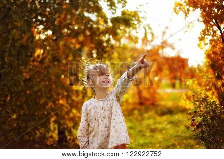 Happy girl pointing at the sky in autumn