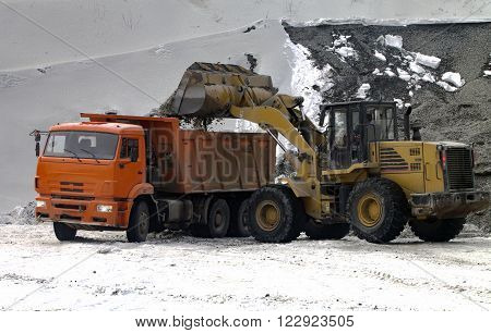 Front end loader is unloading scoop with gravel into dump truck in winter day.