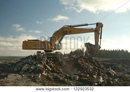 Yellow excavator is digging the hole its shovel is full.