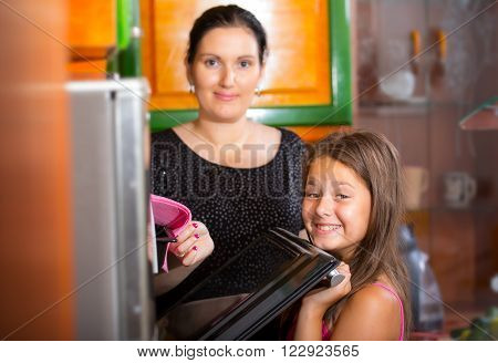 Mother and daughter preparing dinner together in the kitchen