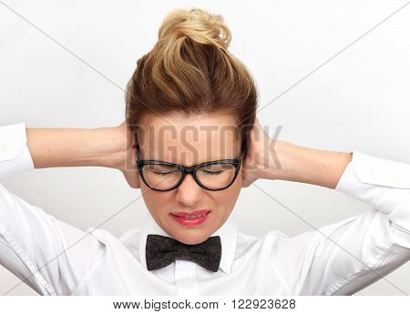 Young woman is going through some tough times. Woman covering his ears with his hands.