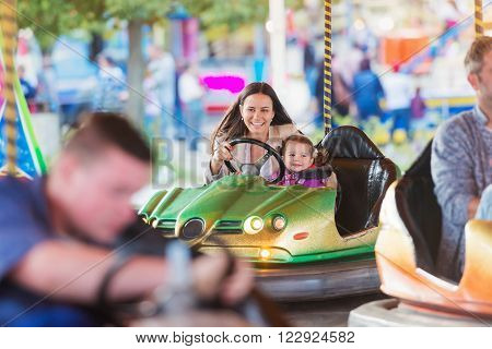 Cute little girl with her mother having fun at fun fair, driving a bumper car, amusement park ** Note: Visible grain at 100%, best at smaller sizes