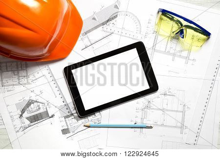 Blueprint on table with helmet tablet and safety glasses.