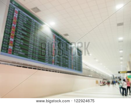 Blurred airport electronic display screen flight timetable of departures and passengers are waiting around. Airport Departure Board.